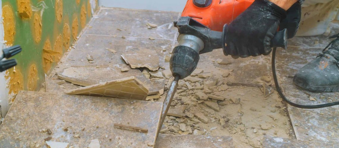 Removal of old floor during a renovation of housing from demolition hammer, fragments of ceramic tiles, dust